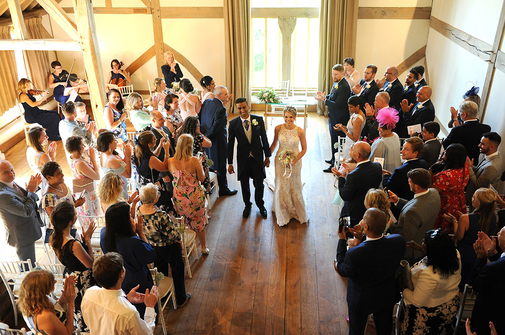 A smiling happy and excited Bride and Groom at Cain Manor Headley Down Surrey walk down the aisle of the Music Room as husband and wife to much applause