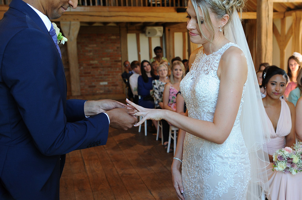 Groom at the wonderfully relaxed and homely wedding venue Cain Manor in Headley Down Surrey eases the wedding ring onto his Bride's finger