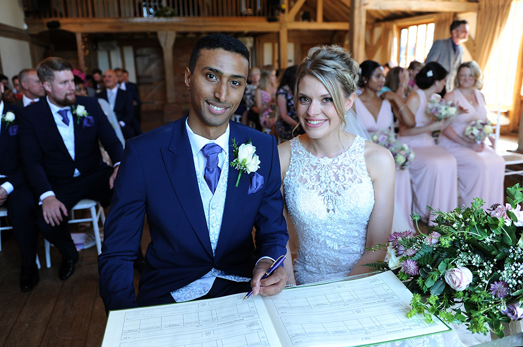Wedding picture of the happy Bride and groom sitting down in the Music Room at Cain Manor in Headley Down Surrey signing the marriage register