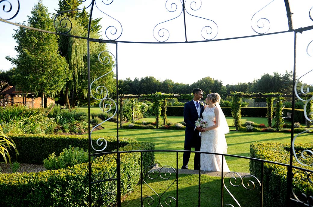 A romantic wedding photo of a newlywed couple looking into each others eyes in the garden at Cain Manor in Surrey captured through the iron pergola