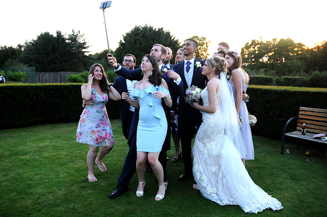Time for a friends' selfie wedding photo at the wonderful Surrey wedding venue Cain Manor out on the lawn during the evening celebrations