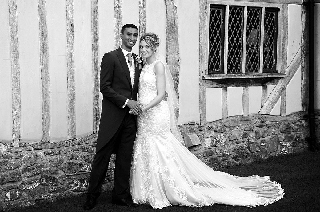 Relaxed and happy Newlywed couple stand before the weather beaten walls of the quaint looking Cain Manor a wonderful wedding venue in Headley Down Surrey