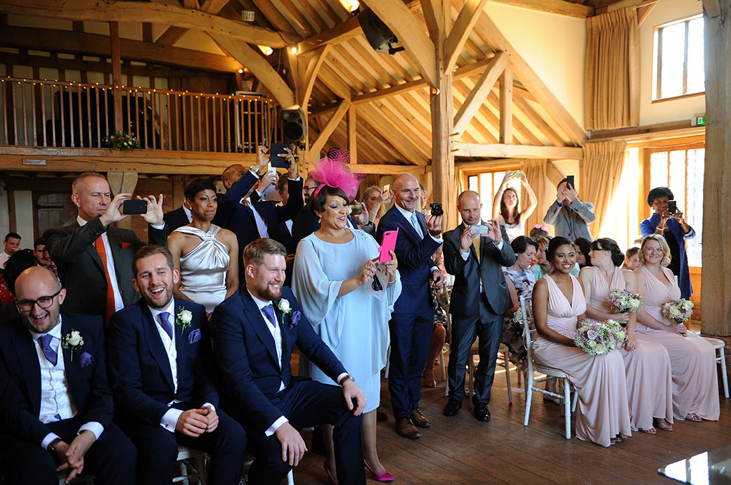 Cameras smiles and action at Surrey wedding venue Cain Manor as wedding guests excitedly line up in the Music Room to get a picture of the happy newlywed couple