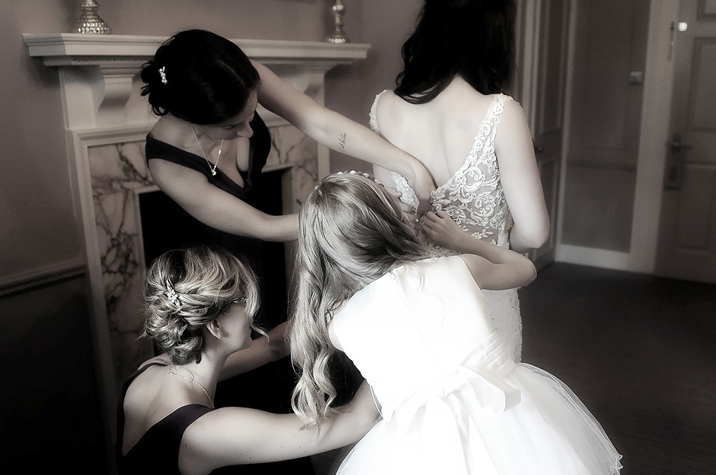 View from behind of busy Bridesmaids as they fasten up the Bride's wedding dress at the welcoming and homely Surrey venue Gorse Hill in the bridal suite