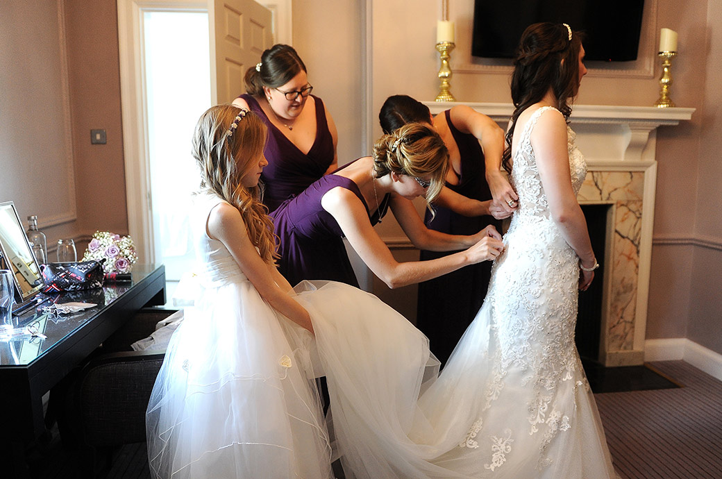Bridesmaids in the Bridal Suite at the popular Surrey Wedding venue Gorse Hill all get stuck in as they fasten up the Bride's wedding dress