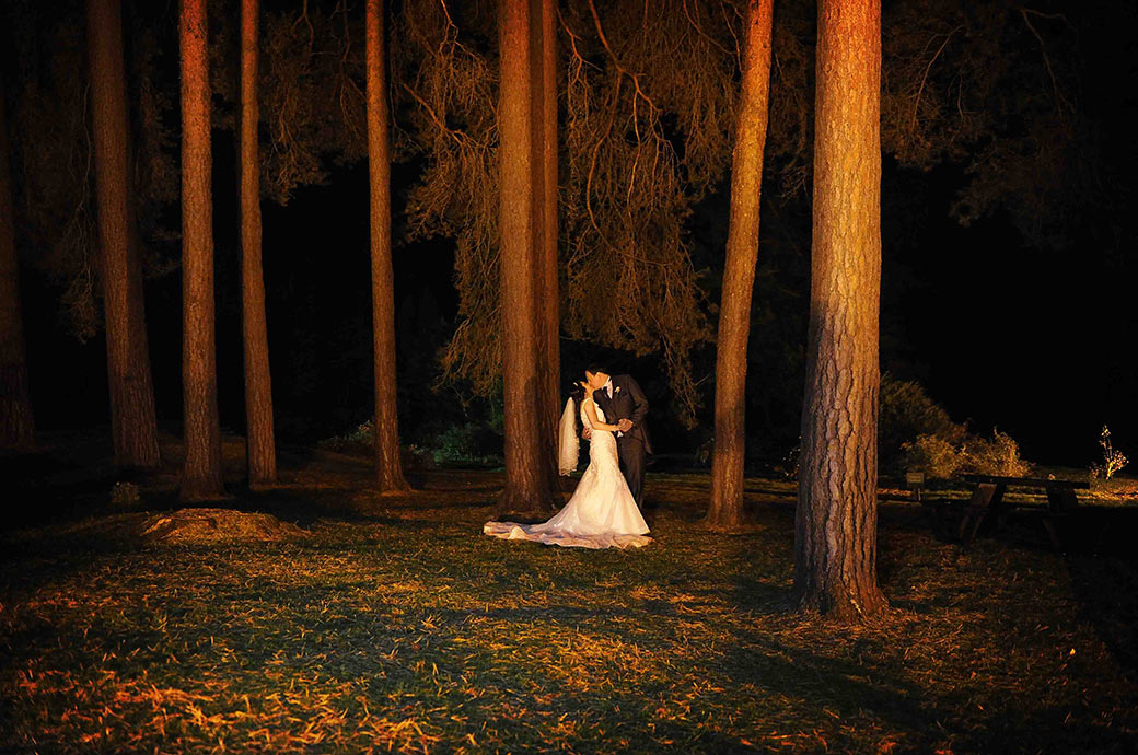 A newlywed couple have a beautiful romantic kiss captured at night time beneath the trees at the ever popular Surrey wedding venue Gorse Hill