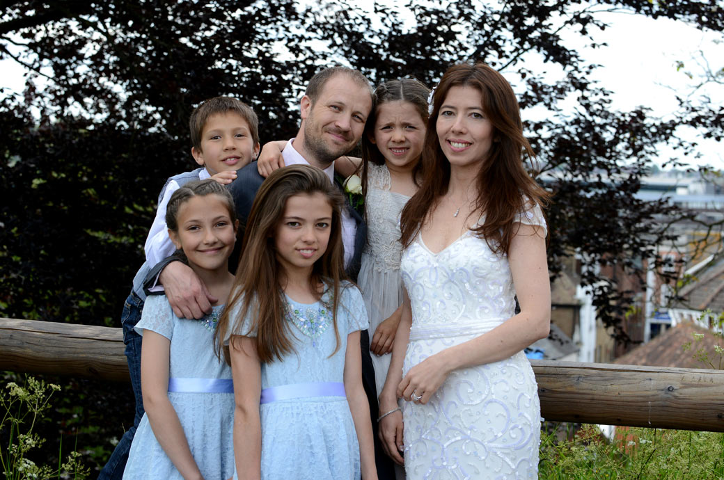 Family wedding photograph of the newlywed couple with their children in the grounds of Guildford Castle Gardens captured by Surrey Lane wedding photographers