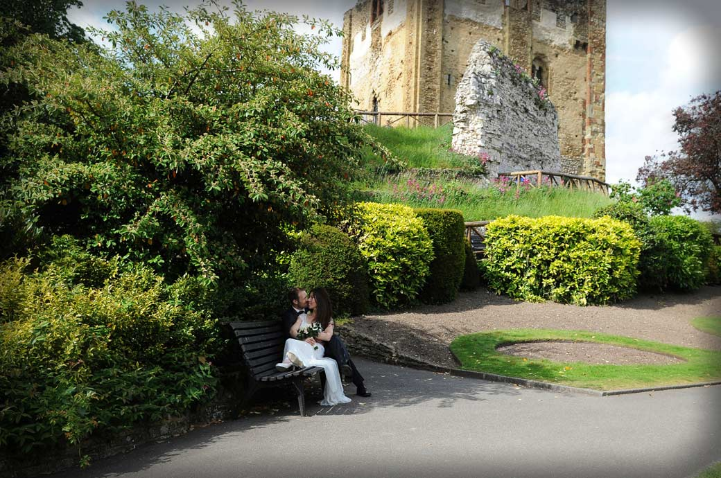 Romantic wedding picture of a Bride and Groom sharing an intimate moment on a park bench in the lovely historic setting of  Guildford Castle Gardens Surrey
