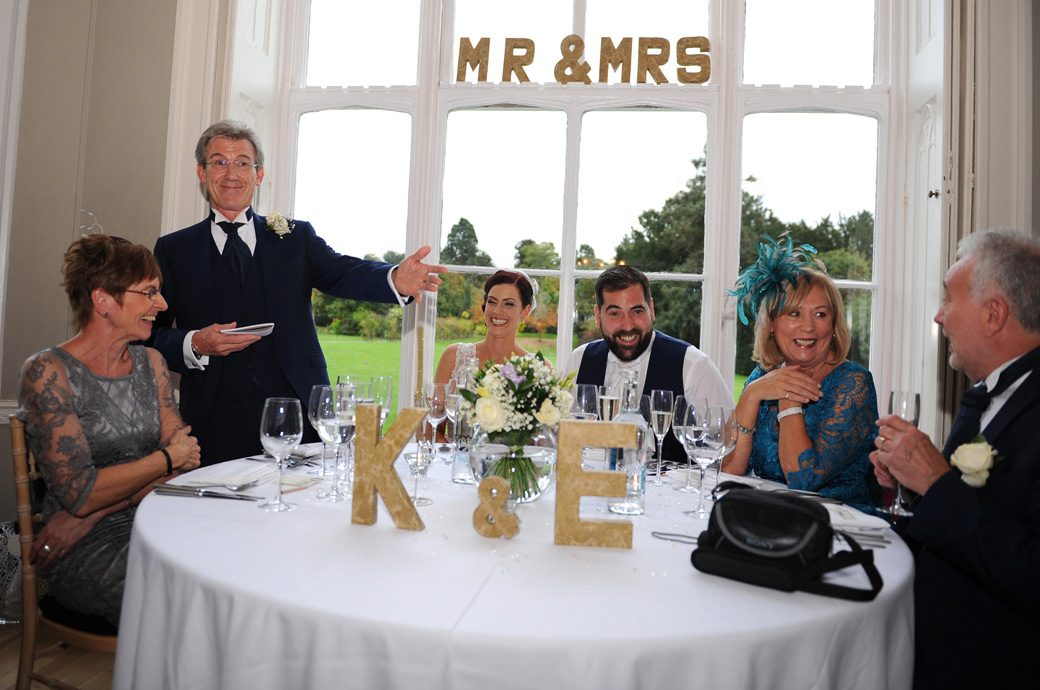 Fun and laughter in this wedding picture taken in the Orchid Room at Nonsuch Mansion in Cheam Surrey at the top table during the father of the bride's speech