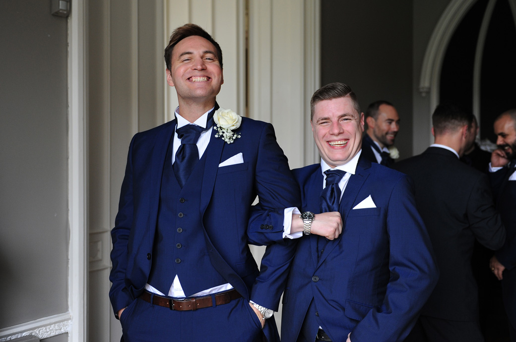 All smiling Groomsmen captured arm in arm in this fun wedding photograph taken prior to the marriage ceremony at Surrey wedding venue Nonsuch Mansion