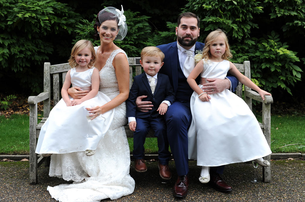 Nonsuch Mansion wedding couple pose with their page boy and flower girls on a garden bench for their Surrey Lane wedding photographer in Cheam Village