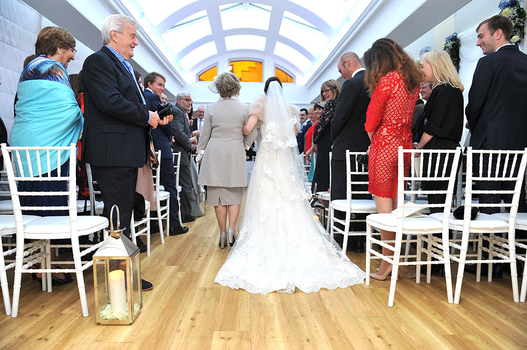 Wedding photo taken from behind as the Bride walks in her mother's arm down the aisle of The Belvedere Suite at Surrey wedding venue Pembroke Lodge in Richmond Park