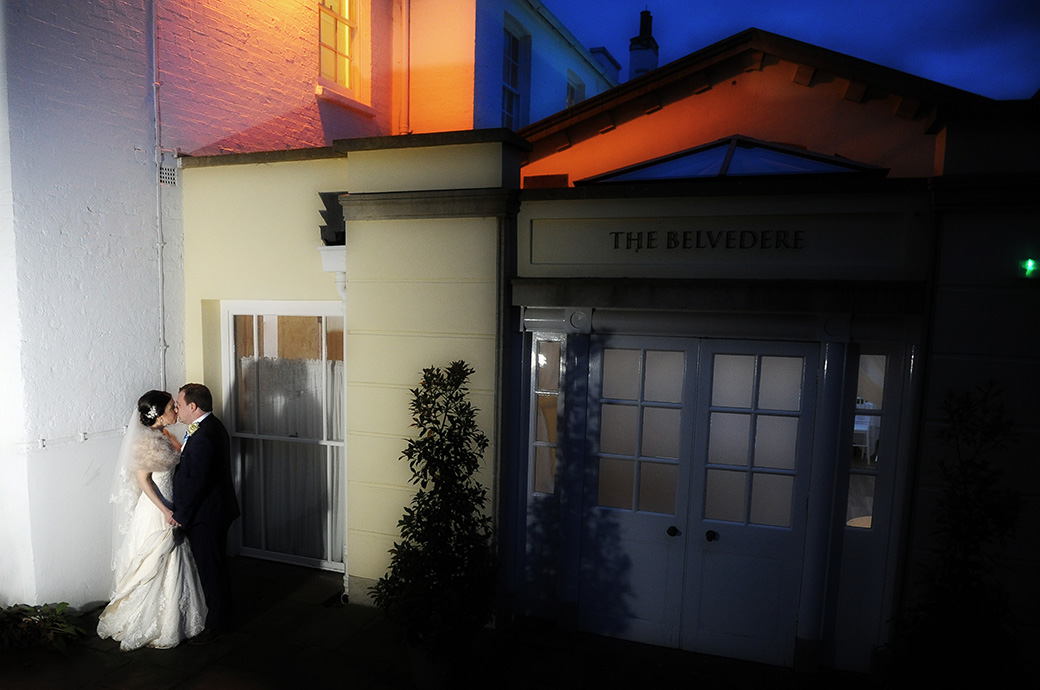 Newlyweds romantically kiss outside The Belvedere Suite at Pembroke Lodge in Richmond Park Surrey at night as they take time out from the celebrations