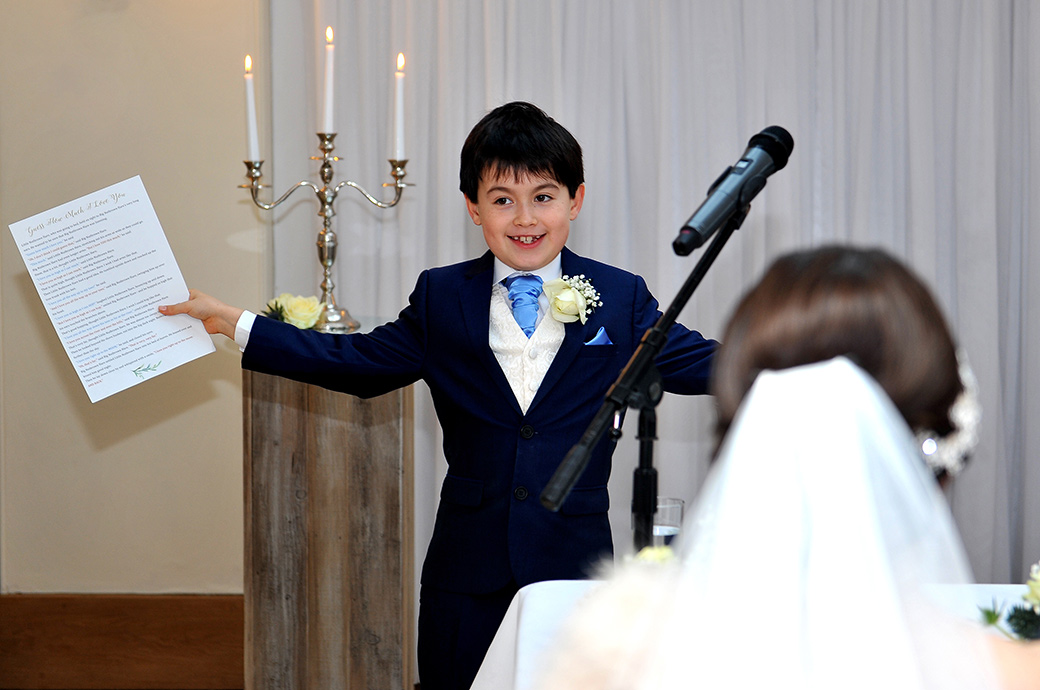 Triumphant sweet pageboy in The Belvedere Suite at Surrey wedding venue Pembroke Lodge accepts the applause after his very entertaining marriage ceremony reading