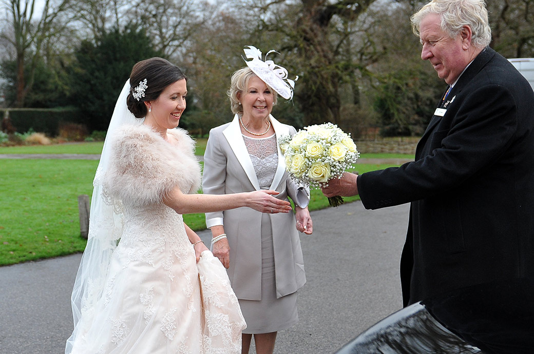 A smiling Mother watches as her daughter is handed her wedding bouquet outside the Pembroke Lodge venue in the wonderful Richmond Park in Surrey