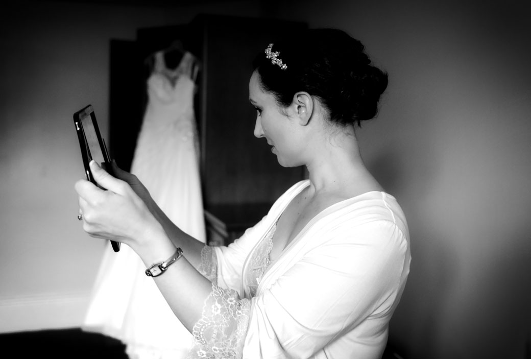 A bride checks her hair in a mirror in this evocative wedding photograph captured by Surrey Lane wedding photography at the magnificent Wotton House