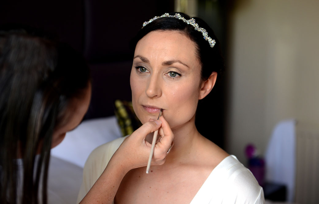 Lipstick is applied as the Bride reflects on her imminent marriage captured in this serene wedding photograph from Surrey wedding venue Wotton House