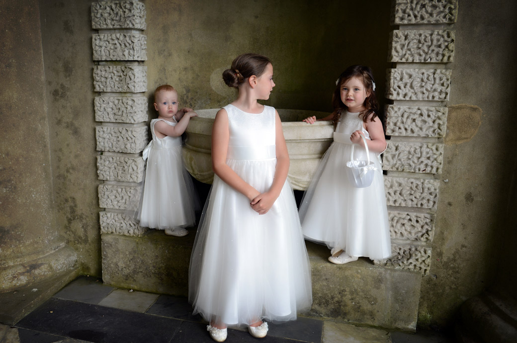 Cute and lovely bridesmaids play around in one of the alcoves in this wedding picture taken by a Surrey Lane wedding photographer in the Wotton House Roman Temple