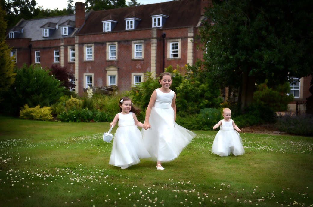 Beautiful wedding photo of three small bridesmaids playing and having fun on the lawn captured by Surrey Lane wedding photography at Wotton House Dorking