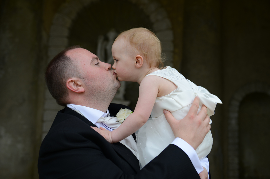 Groom gives his adorable little bridesmaid daughter a tender kiss in thie sweet wedding picture taken at the wonderful Surrey wedding venue Wotton House Dorking