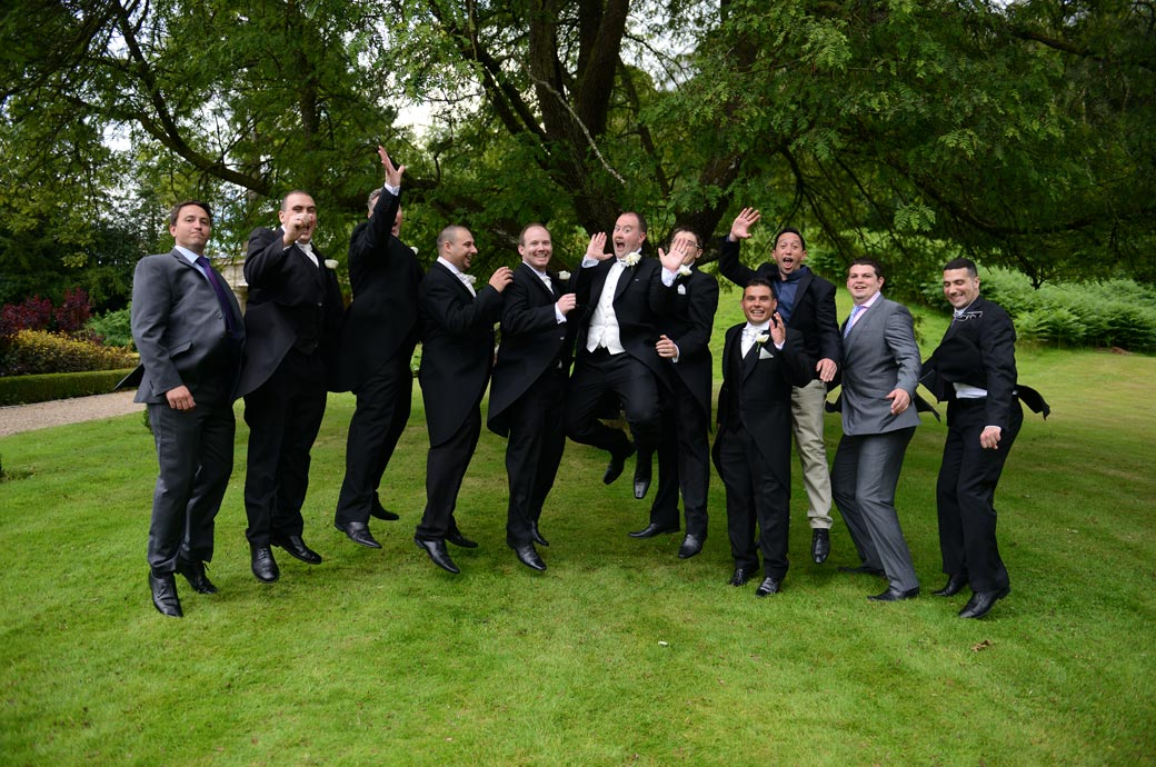 Getting some air in this funny group wedding photo as the boys jump up taken at the lovely Wotton House Dorking a fine and popular Surrey wedding venue
