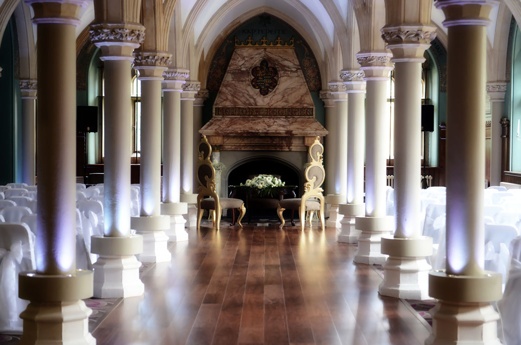 Past the pillars zooming in on the grand wedding chairs in this dream like wedding picture by Surrey Lane wedding photographers in Wotton House's beautiful Old Library