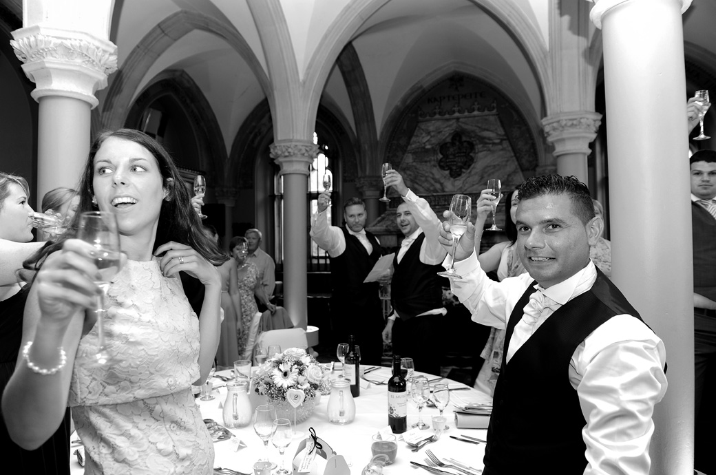 Everyone raises their glasses to toast the newly-weds in this wedding photo by Surrey Lane wedding photographers after the speeches at Wotton House Dorking in the Old Library