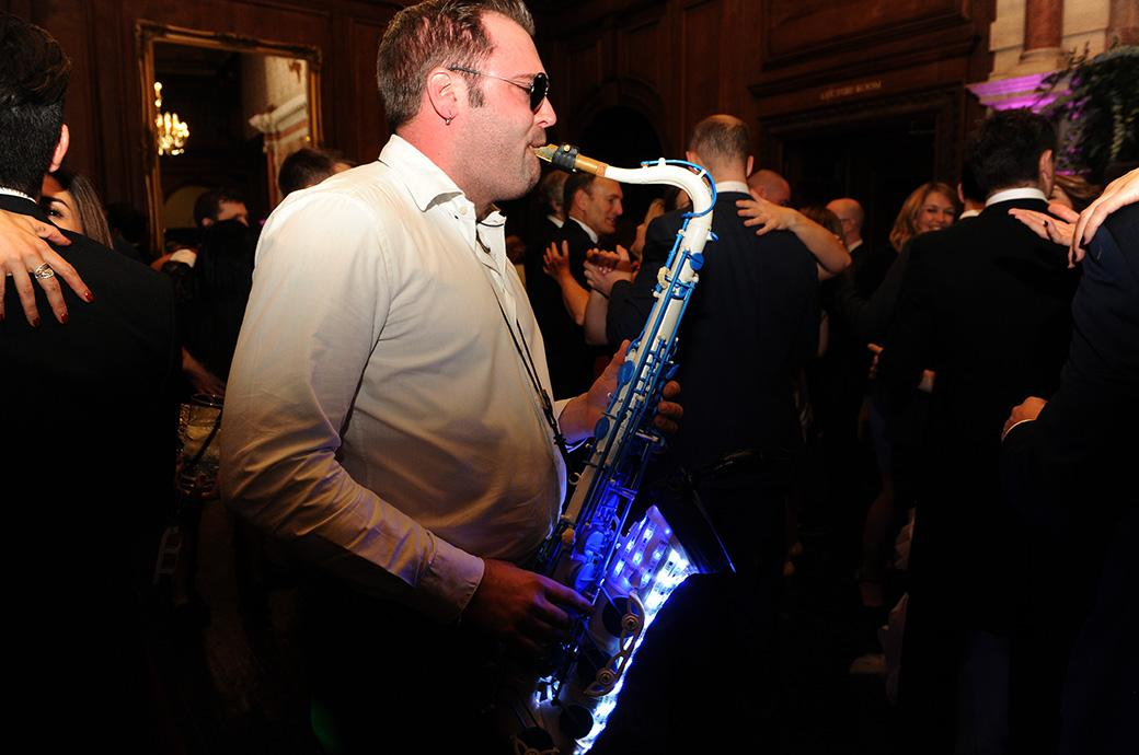 Unusual wedding photo taken at Surrey wedding venue Addington Palace in Croydon of a saxophonist on the Great Hall dancefloor playing a luminous lit up saxophone