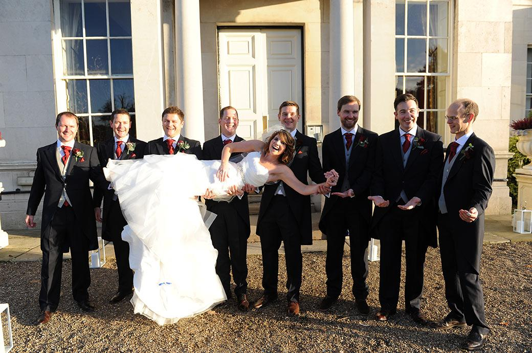 Beautiful smiling Bride is held up by the Groom and Groomsmen at the grand and impressive Addington Palace Croydon Surrey in this relaxed informal wedding picture
