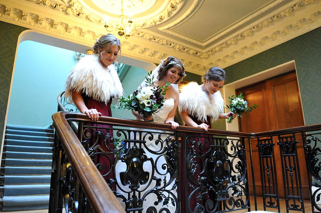 Bride and Bridesmaids looking over the banister at final arrival of wedding guests below in this fun wedding picture from Surrey wedding venue Addington Palace