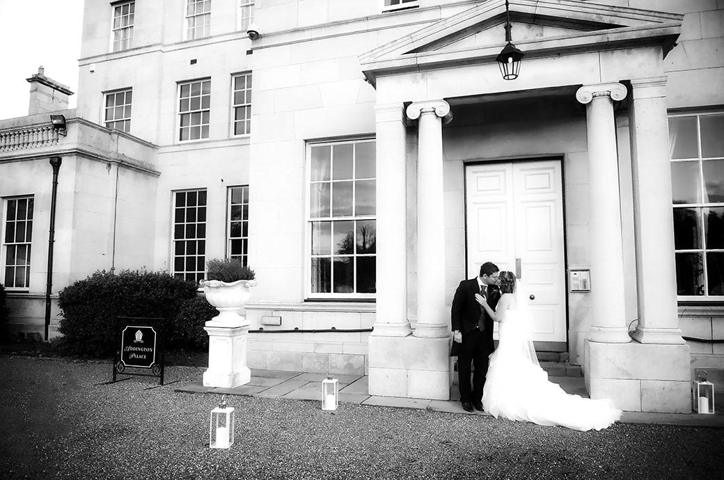 Wedding photograph of a romantic bride and groom kissing in front of the large and impressive columns of Addington Palace an old and stately Surrey wedding venue in Croydon