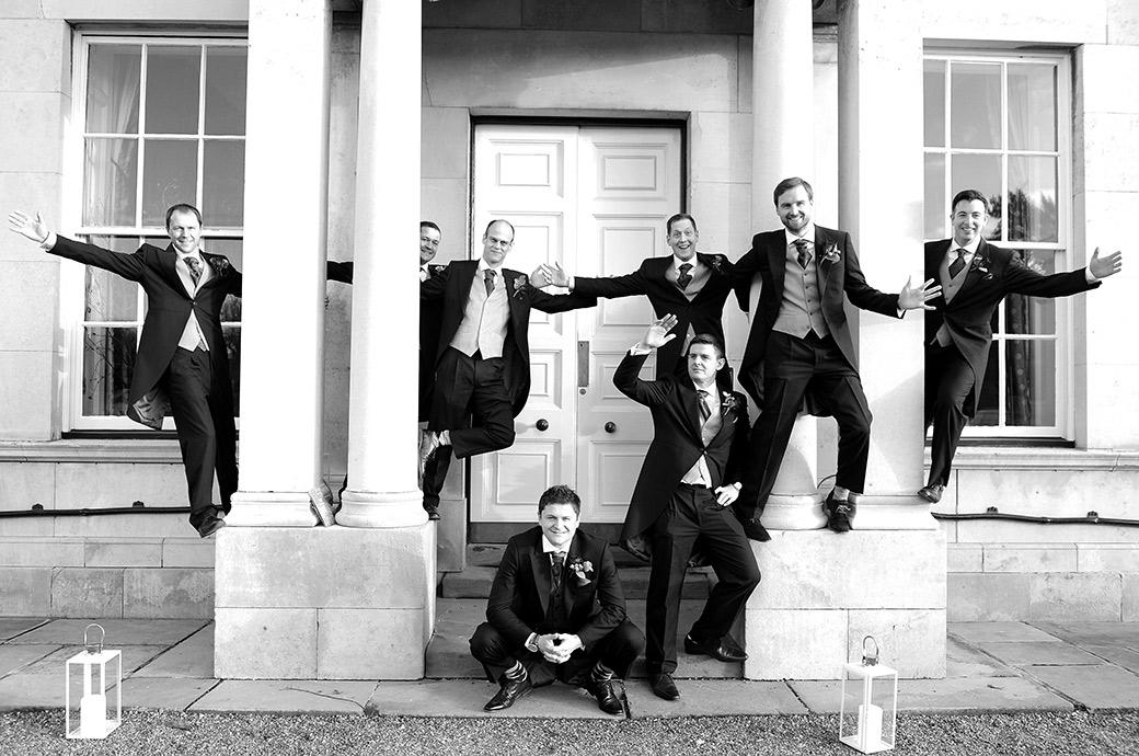 Groom sits on step outside the grand Surrey wedding venue Addington Palace whilst his groomsmen pose on and around the columns in this relaxed and fun group wedding photo
