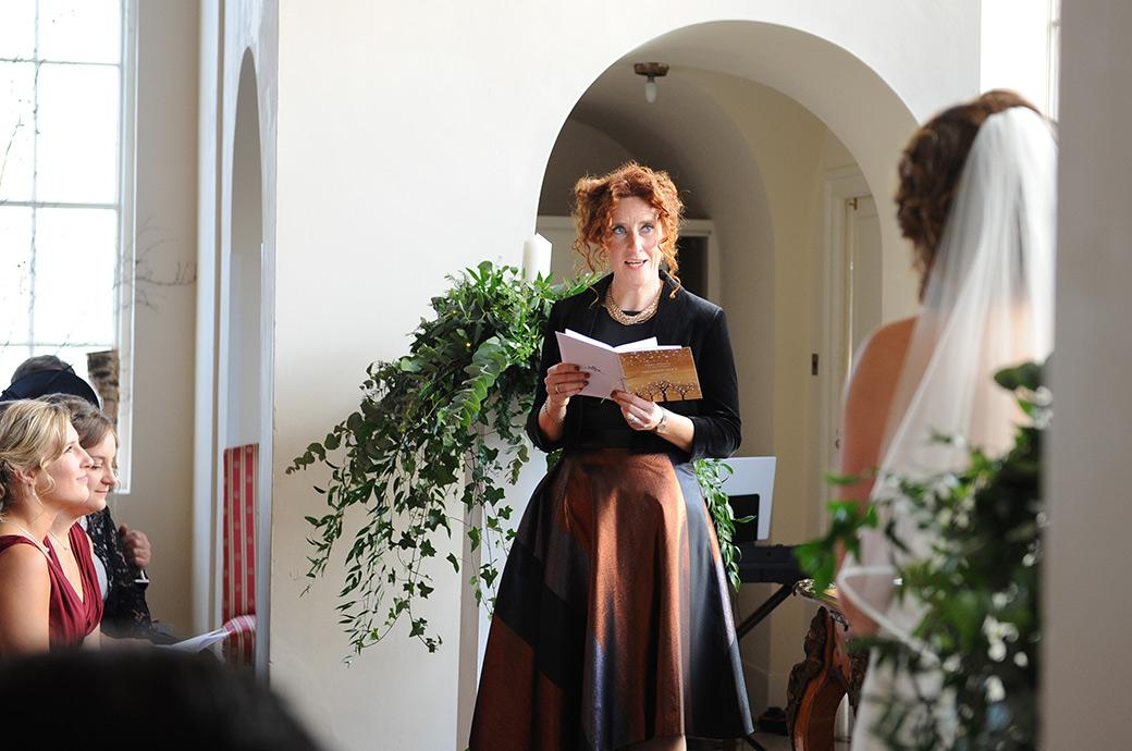 A captivating wedding guest with red hair and piercing blue eyes in the chapel at Surrey wedding venue Addington Palace addresses the young lovers during a reading