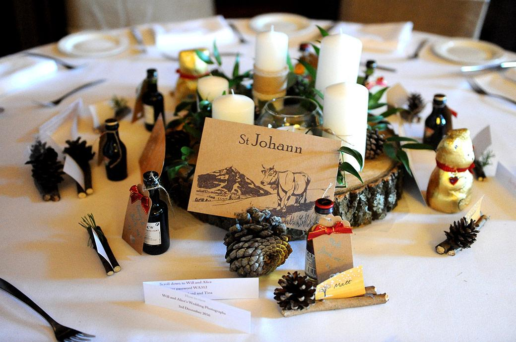 Wedding breakfast table settings at Addington Palace in Croydon Surrey comprising a ski resort table name complete with fir cones candles and miniature bottles of spirits