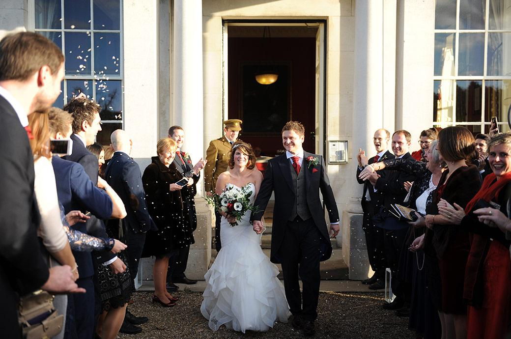 Beaming Bride and groom at the impressive and historical Addington Palace in Croydon Surrey walk out into the sunshine outside underneath a long line of confetti throwing guests