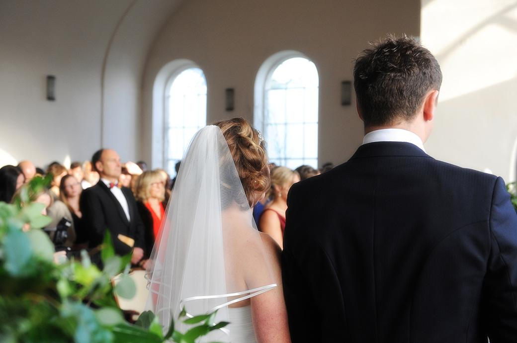 Wedding photograph taken from behind the Bride and groom as they listen to the engaging readings in the Chapel at the historic Addington Palace Surrey wedding venue