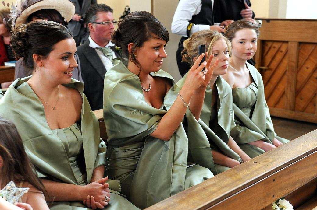 A smiling Bridesmaid captures the moment with her camera in this lovely natural wedding picture taken at Addiscombe Catholic Church a wedding venue in Croydon Surrey