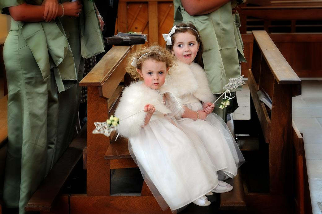 Two cute little Bridesmaids sit playing with their wands in this delightful wedding photo captured at Surrey wedding venue Addiscombe Catholic Church down in the pews