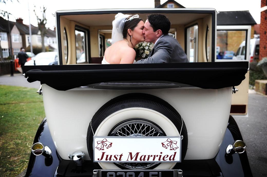 A just married couple kiss in their open top car in this romantic wedding picture taken outside Addiscombe Catholic Church Our Lady of the Annunciation a Surrey wedding venue