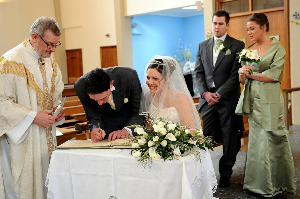 A delighted Bride smiles as her husband signs the register is this lovely natural wedding photograph taken at Addiscombe Catholic Church by Surrey Lane wedding photographers