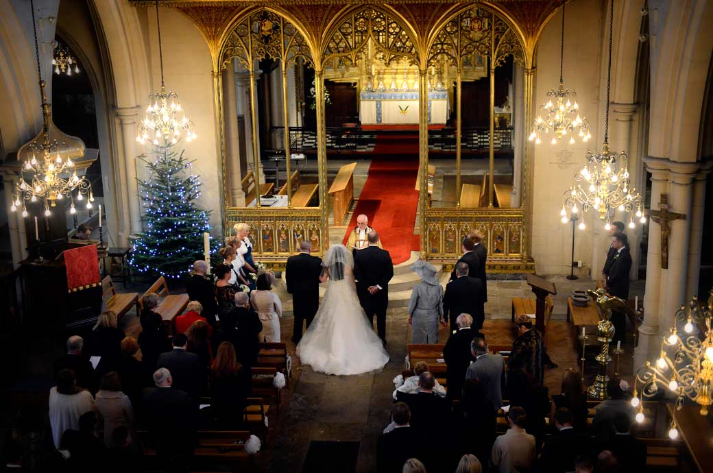 Ariel wedding photograph of the service taken from the balcony including the Christmas tree and gold chancel at All Saints Carshalton in Surrey