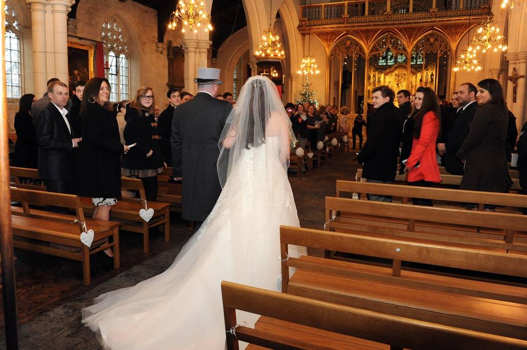 A wedding picture of the guests turning round to see the bride as she walks past down the aisle at Carshalton All Saints Church