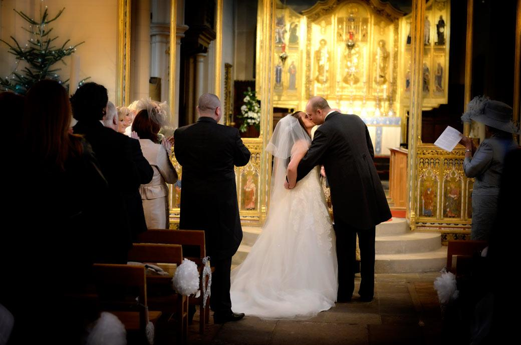 A romantic Christmas kiss wedding photograph taken before the golden chancel in the historic and ancient All Saints Carshalton, Surrey