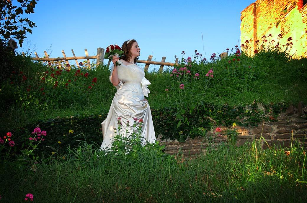 Lovely Bride walking on a path past the flowers to Guildford Castle wedding photo taken after a service at Surrey wedding venue The Angel Posting House