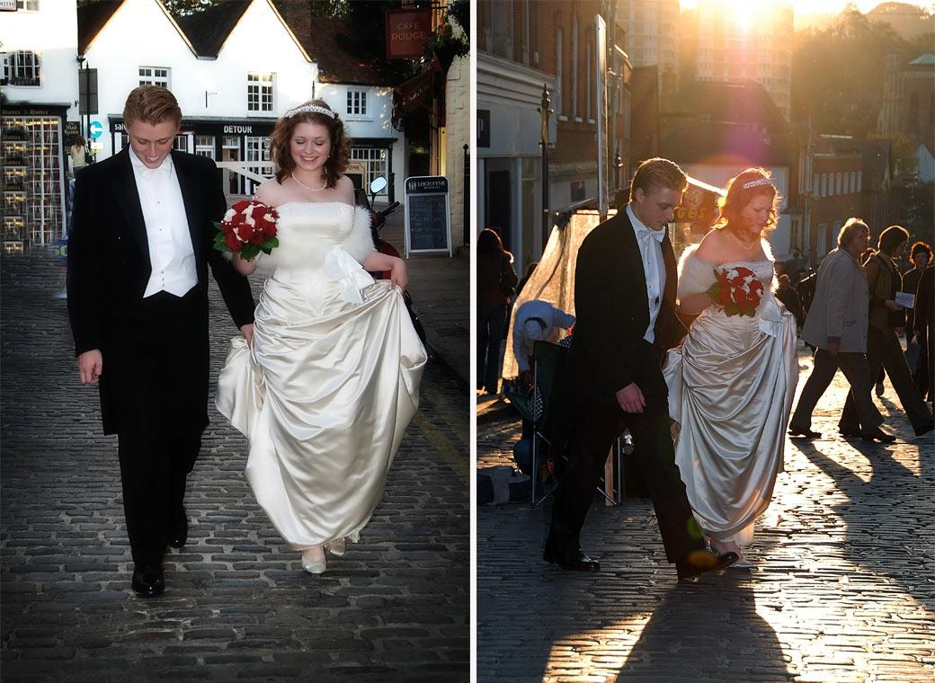 Happy carefree young newly-weds walk the cobbles in this wedding photograph taken on route to The Angel Posting House from nearby Guildford Castle