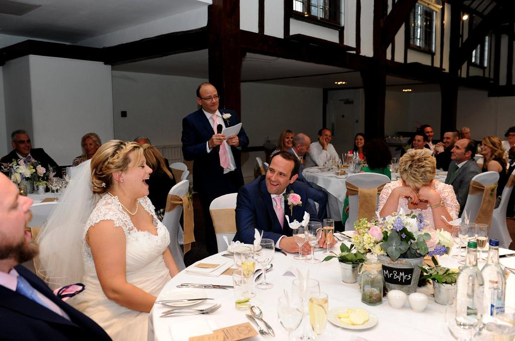 The Best Man starts his verbal assault on the Groom in his funny speech which gets everyone at the head table in stitches in Surrey in the Burford Bridge Hotel's Tithe Barn