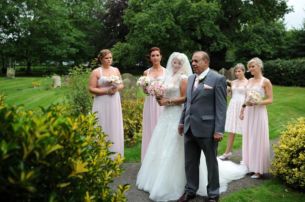 Bride smiles as her father arrives to take her into church to get married followed by a Burford Bridge Hotel reception captured by a Surrey Lane wedding photographer