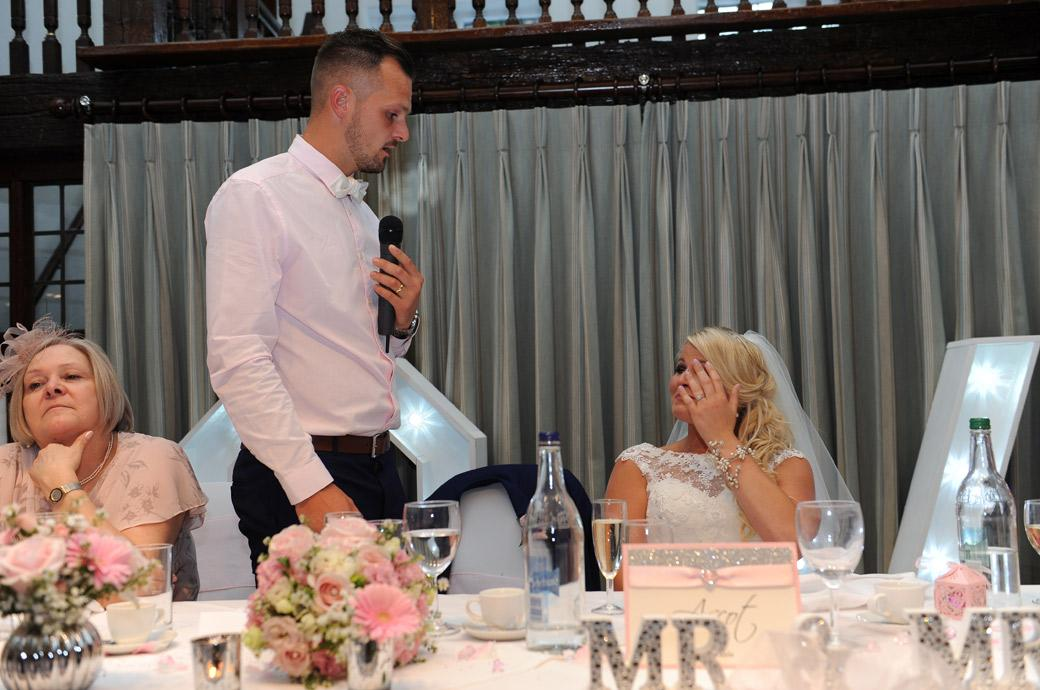 Bride wipes a tear from her eye as the Groom delivers a heartfelt personal message in The Tithe Barn at Burford Bridge Hotel Surrey during the wedding speeches