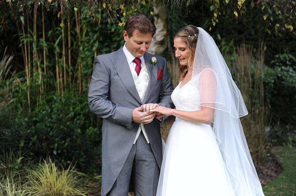 Newlyweds at Surrey wedding venue Burford Bridge Hotel take time out to admire their wedding rings captured in the relaxed and tranquil garden area