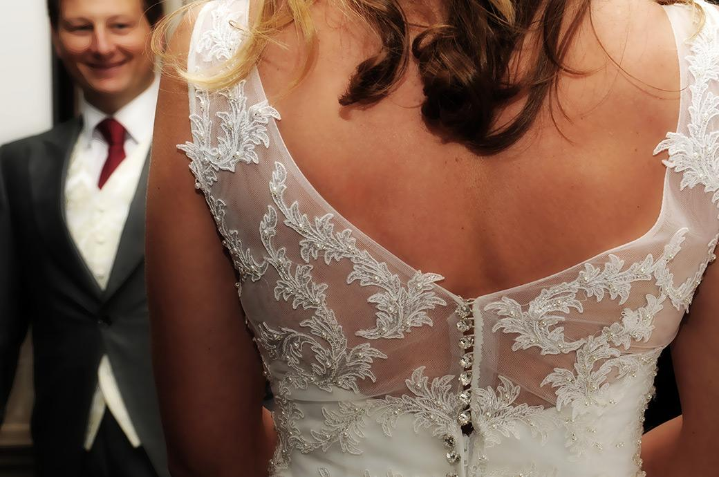 The beautiful back of the Bride's wedding dress captured as she talks to her smiling Groom in the Tithe Barn at the Burford Bridge Hotel Surrey wedding venue
